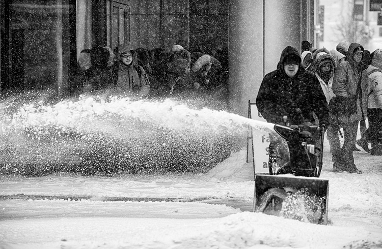 A man with a snow blower clears a side walk on King Street East after Toronto was hit with over 25 cm of snow yesterday.